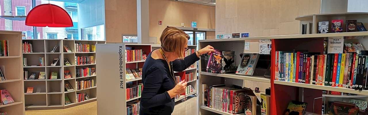 En person tittar på böcker på bibliotekets barnavdelning